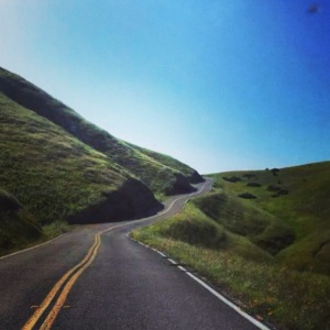 Winding road and green rolling hills.